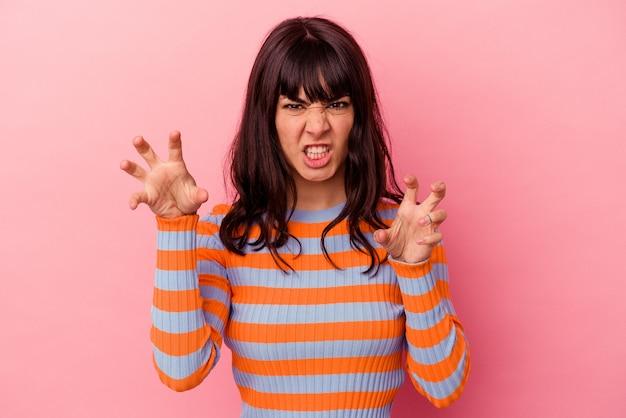 ピンクの背景に分離された若い白人女性は、猫を模倣した爪、攻撃的なジェスチャーを示しています。