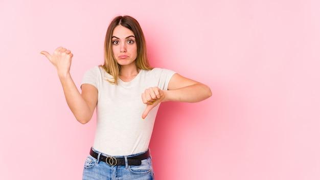 親指を上に、親指を下に表示するピンクの背景に分離された若い白人女性、難しい選択の概念