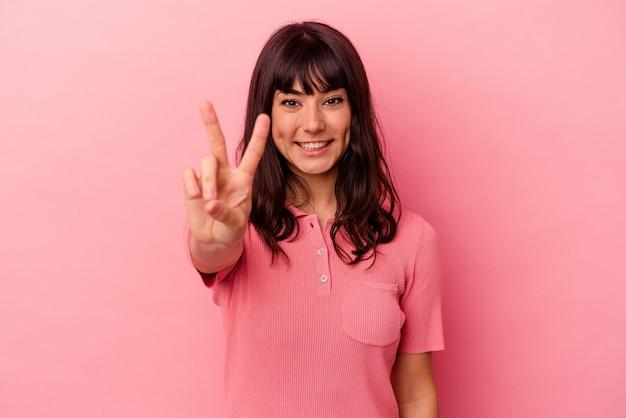 승리 기호를 표시 하 고 광범위 하 게 웃 고 분홍색 배경에 고립 된 젊은 백인 여자.