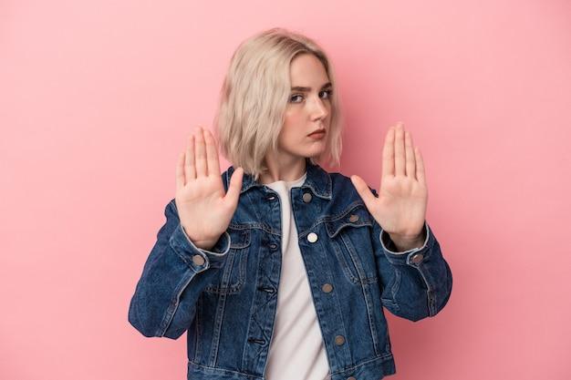 분홍색 배경에 고립된 젊은 백인 여성이 손을 뻗은 채 정지 신호를 보여주며 당신을 방해합니다.