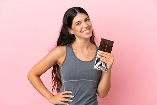 Молодая кавказская женщина изолирована на розовом фоне, принимая шоколадную таблетку и счастливая
