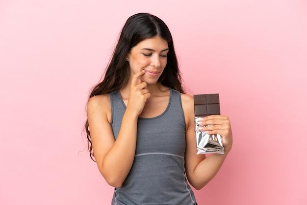 Молодая кавказская женщина изолирована на розовом фоне, принимая шоколадную таблетку и сомневаясь