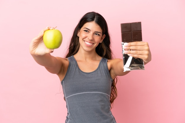 片手にチョコレートタブレットともう片方の手にリンゴを取っているピンクの背景に分離された若い白人女性