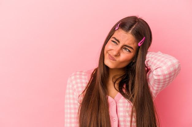 Молодая кавказская женщина изолирована на розовом фоне, касаясь затылка, думая и делая выбор.