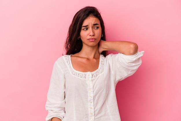 분홍색 배경에 고립된 젊은 백인 여성은 머리 뒤쪽을 만지고 생각하고 선택합니다.