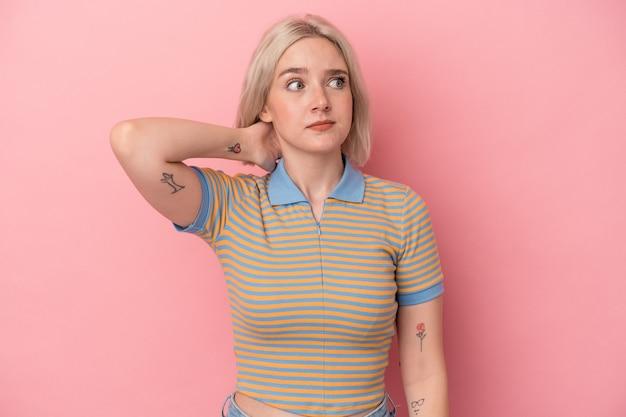 頭の後ろに触れて、考えて、選択をするピンクの背景に分離された若い白人女性。