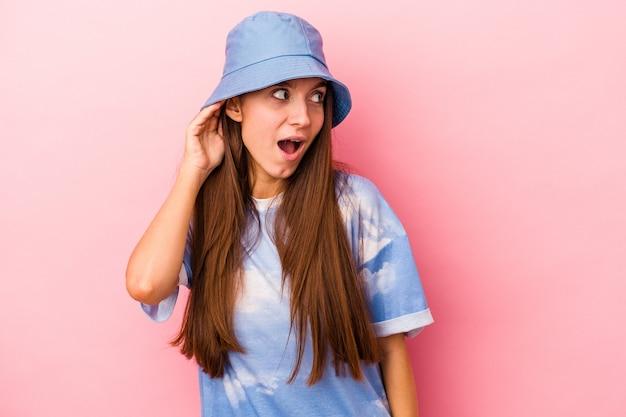 ゴシップを聴こうとしているピンクの背景に分離された若い白人女性。