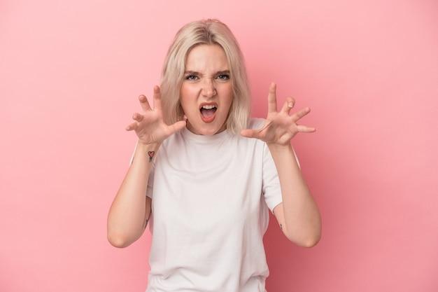 ピンクの背景に孤立した若い白人女性は、緊張した手で叫んで動揺します。