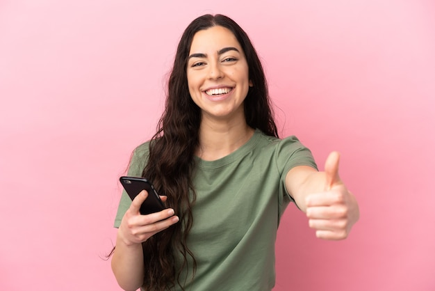 엄지 손가락을하는 동안 휴대 전화를 사용하여 분홍색 배경에 고립 된 젊은 백인 여자