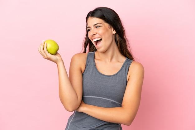 リンゴと幸せなピンクの背景に分離された若い白人女性