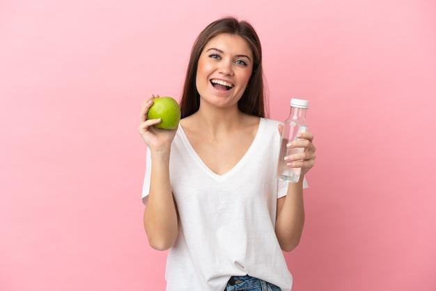 사과와 물 한 병 분홍색 배경에 고립 된 젊은 백인 여자