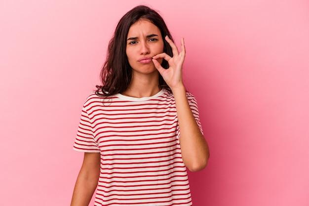 Молодая кавказская женщина изолирована на розовом фоне с пальцами на губах, сохраняя в секрете.