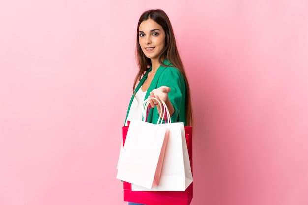 ショッピングバッグを保持し、誰かにそれらを与えるピンクで隔離の若い白人女性