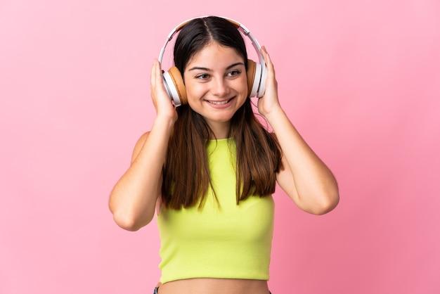 Молодая кавказская женщина изолирована на розовой слушающей музыке
