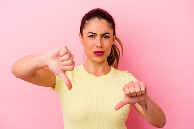 ピンクで孤立した若い白人女性は、両方の親指を上げて、笑顔で自信を持っています。