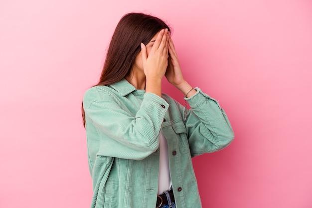 손으로 눈을 덮고 두려워 분홍색 벽에 고립 된 젊은 백인 여자.