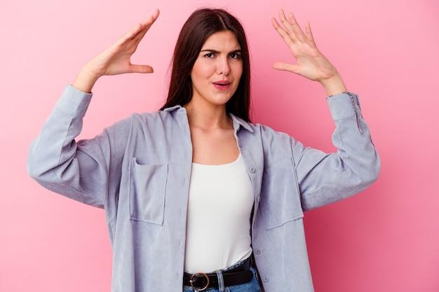승리 또는 성공을 축하하는 분홍색 벽에 고립 된 젊은 백인 여자, 그는 놀라고 충격
