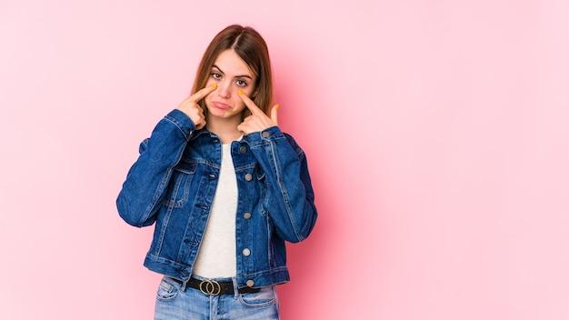 泣いているピンクの壁、何か、苦痛と混乱の概念に不満に分離された若い白人女性。