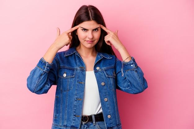 분홍색 벽에 고립 된 젊은 백인 여자는 머리를 가리키는 집게 손가락을 유지하는 작업에 집중했다.