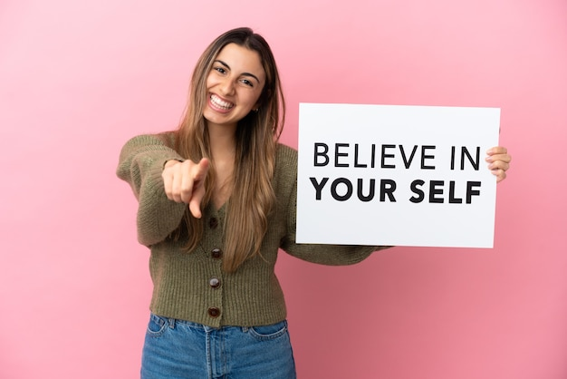 Молодая кавказская женщина изолирована на розовой стене, держа плакат с текстом «верь в себя» и указывая вперед