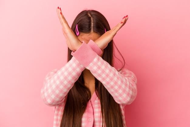 Молодая кавказская женщина изолирована на розовой стене, держа две скрещенные руки, концепция отрицания.