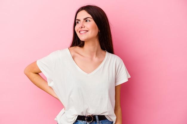 분홍색 벽에 고립 된 젊은 백인 여자는 행복하게 웃음과 뱃속에 손을 유지하는 재미가있다
