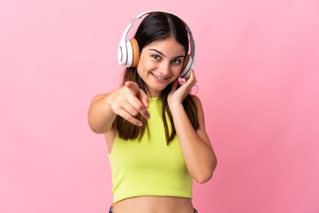 音楽を聴いて正面を指してピンクの壁に孤立した若い白人女性