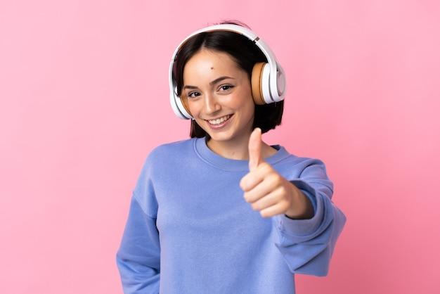 Молодая кавказская женщина изолирована на розовой стене, слушая музыку и с пальцем вверх