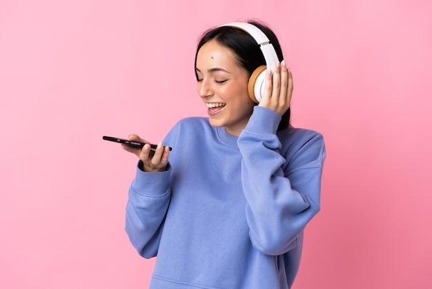 Молодая кавказская женщина изолирована на розовой стене, слушает музыку с мобильного телефона и поет