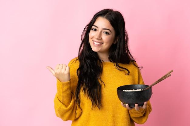 젓가락으로 국수 그릇을 들고 제품을 제시하기 위해 측면을 가리키는 분홍색 벽에 고립 된 젊은 백인 여자