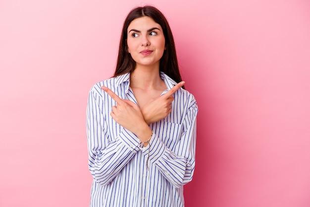 Молодая кавказская женщина, изолированная на розовой стене указывает боком, пытается выбрать один из двух вариантов.