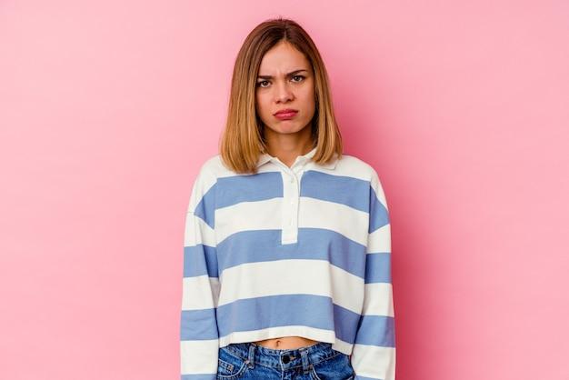 ピンクの壁に孤立した若い白人女性悲しい、深刻な顔、悲惨で不快な感じ。