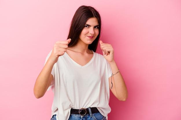 전면에 주먹을 보여주는 분홍색 벽에 고립 된 젊은 백인 여자, 공격적인 표정