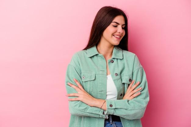 Молодая кавказская женщина изолирована на розовой стене, уверенно улыбаясь со скрещенными руками