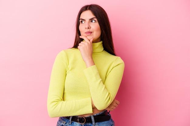 분홍색 벽에 고립 된 젊은 백인 여자 생각 하 고 찾고, 반사 되 고, 숙고, 환상을 갖는
