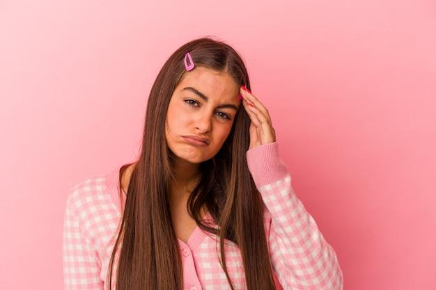 ピンクの壁に孤立した若い白人女性は疲れていて、頭に手を置いて非常に眠いです。