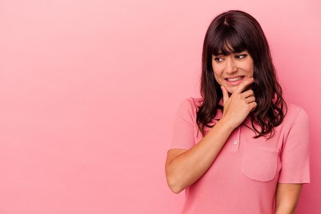 ピンクの壁に孤立した若い白人女性が頭の後ろに触れ、考え、選択をします。