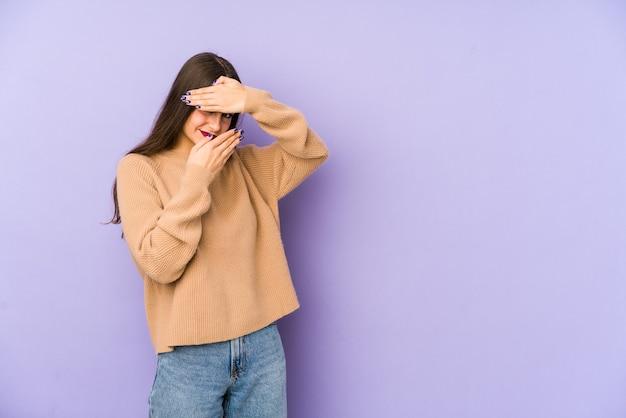Молодая кавказская женщина, изолированная на фиолетовом фоне, моргает в камеру через пальцы, смущенно закрывая лицо.
