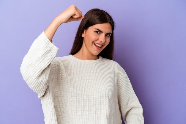 紫色の背景に孤立した若い白人女性は、屈託のない、興奮して応援します。勝利のコンセプト。