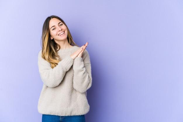 紫色の背景に孤立した若い白人女性は、エネルギッシュで快適な感じ、自信を持って手をこすります。