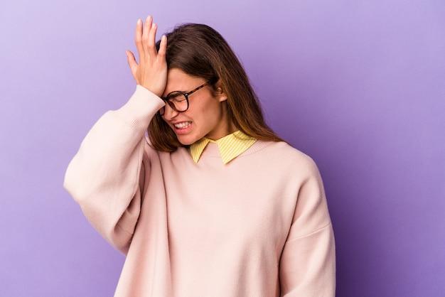 紫色の背景に孤立した若い白人女性は、何かを忘れて、手のひらで額を叩き、目を閉じます。