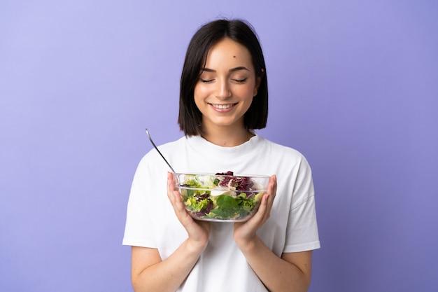 幸せな表情でサラダのボウルを保持している紫色の背景に分離された若い白人女性