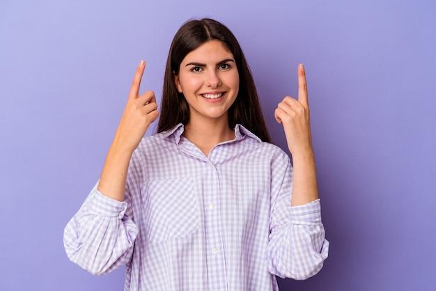 보라색 배경에 고립 된 젊은 백인 여자는 빈 공간을 보여주는 두 앞 손가락으로 나타냅니다.