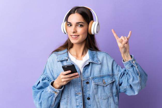 Молодая кавказская женщина изолирована на фиолетовом фоне, слушает музыку с помощью мобильного телефона, делая рок-жест