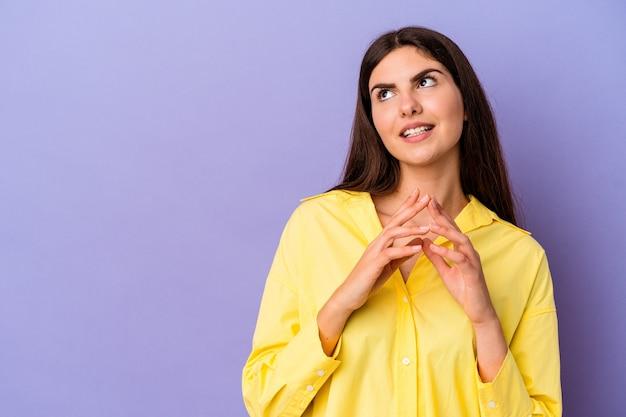 紫色の背景に若い白人女性が計画を立て、アイデアを設定する。