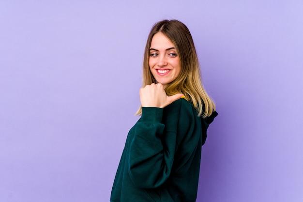 Молодая кавказская женщина, изолированная на фиолетовом фоне, показывает пальцем, смеясь и беззаботно.