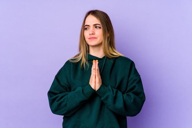 Молодая кавказская женщина, изолированные на фиолетовом фоне, молится, показывая преданность, религиозный человек, ищущий божественного вдохновения.