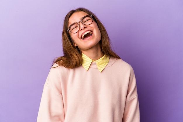 紫色の背景に分離された若い白人女性はリラックスして幸せな笑い、首を伸ばして歯を見せています。