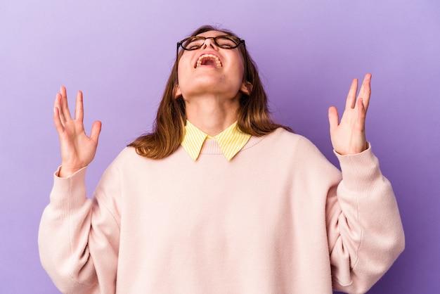 紫色の背景に孤立した若い白人女性が空に向かって叫び、見上げて、欲求不満。