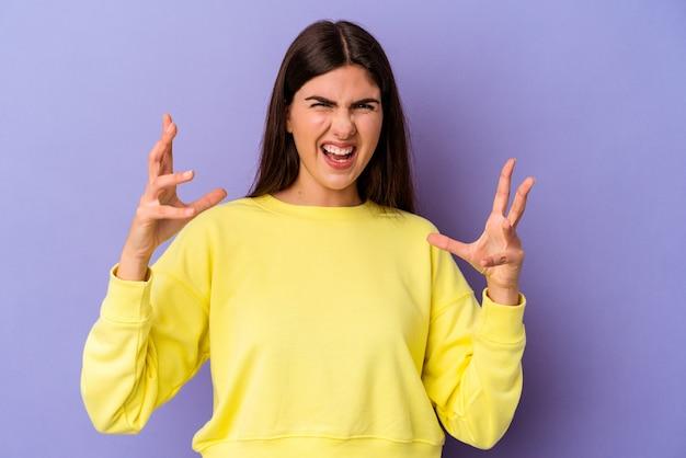 紫色の背景に怒りで叫ぶ若い白人女性。